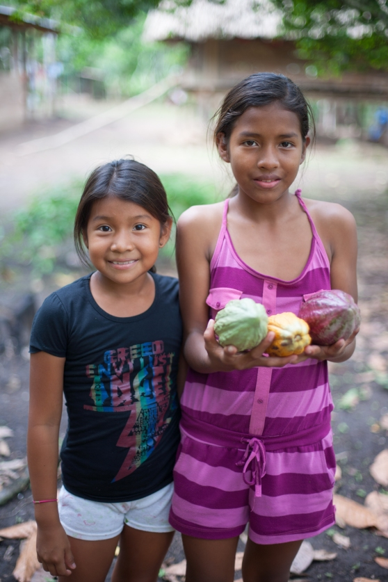 Embera girls holding cacao pods